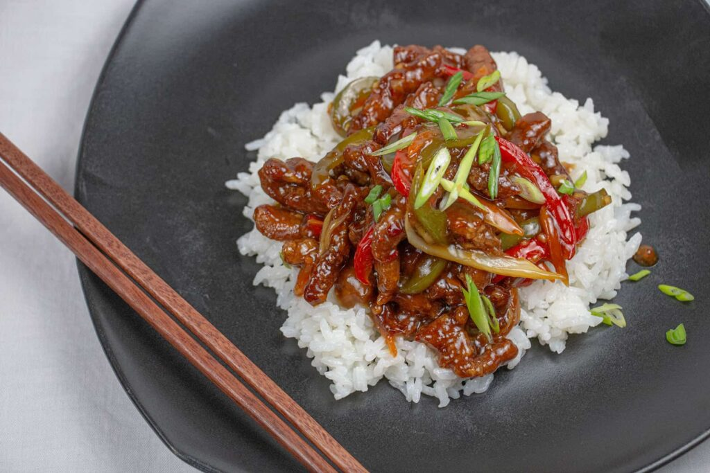 Black plate with chopsticks, rice and beef with peppers.