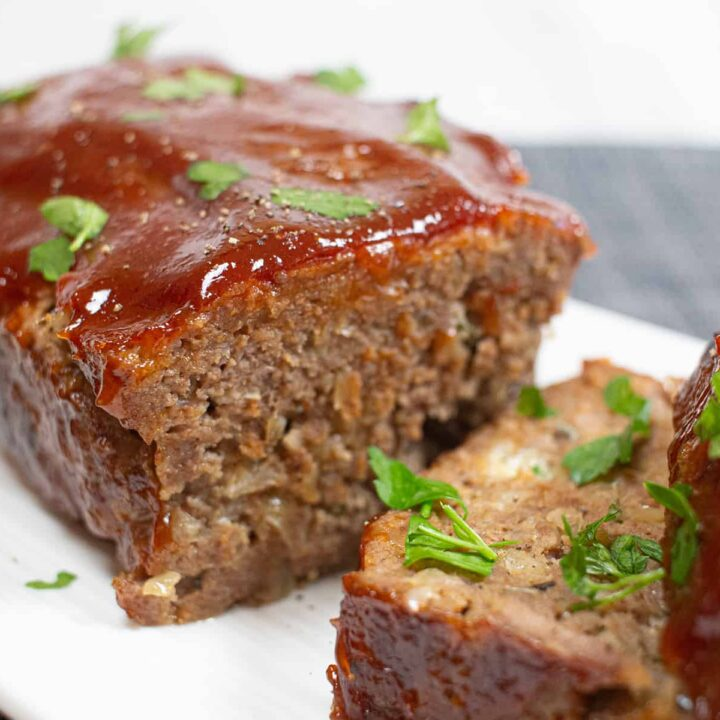 Meatloaf with red glaze on a white plate.