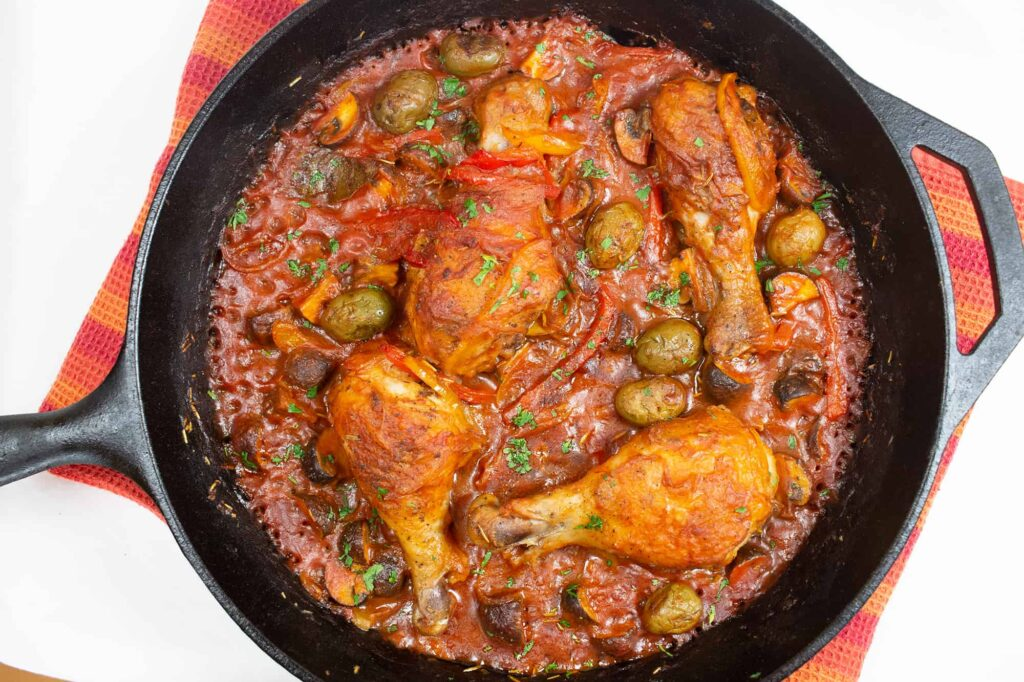 Cast iron skillet with chicken drumsticks in a red sauce.