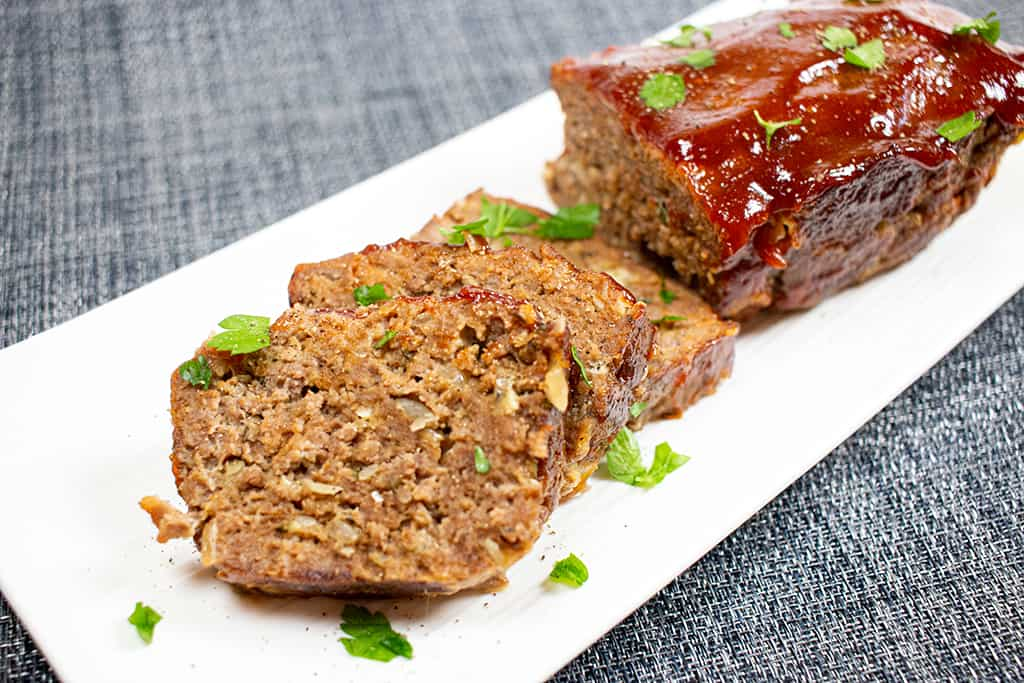 White plate with a meatloaf on it.