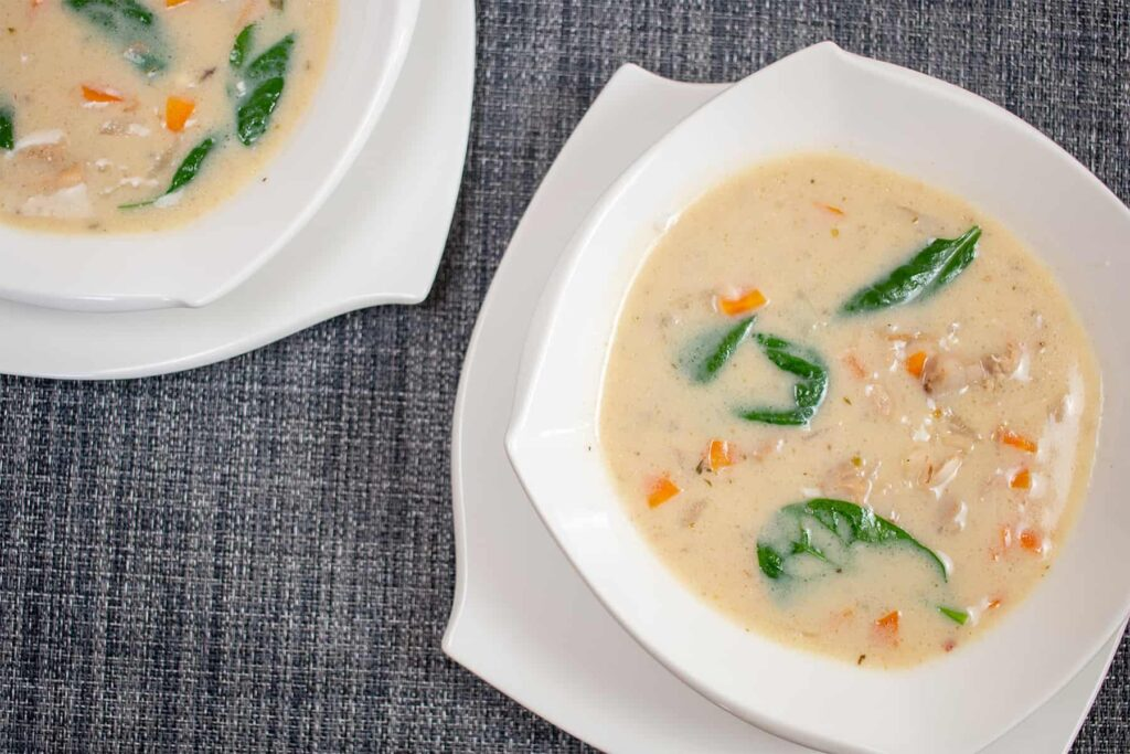 Two white bowls with creamy soup and spinach.