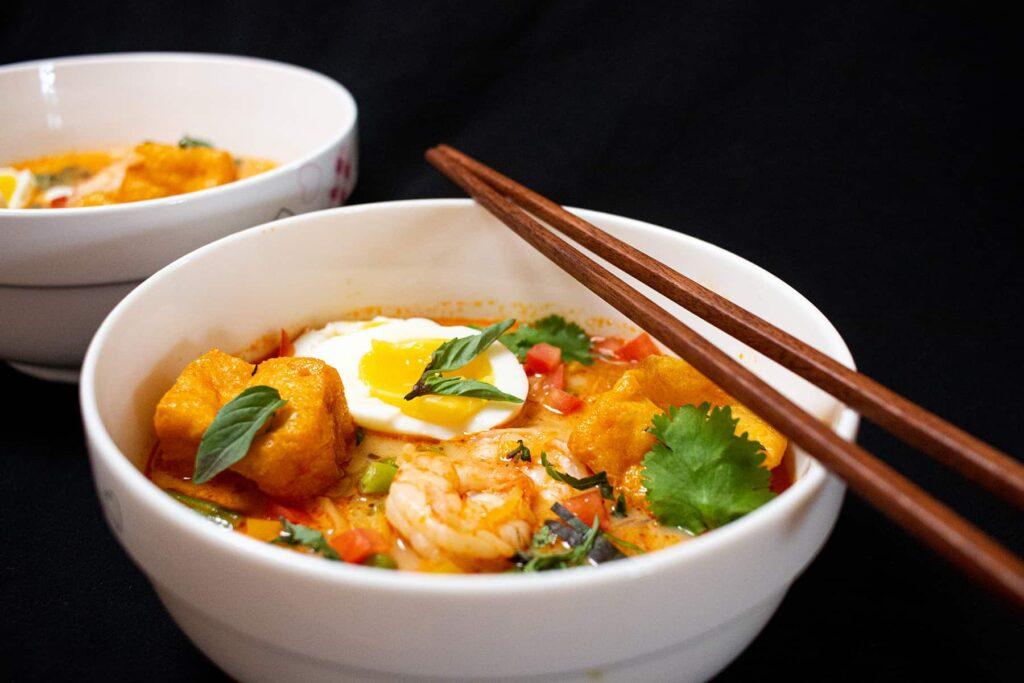White bowl with orange broth, egg, prawn and tofu.