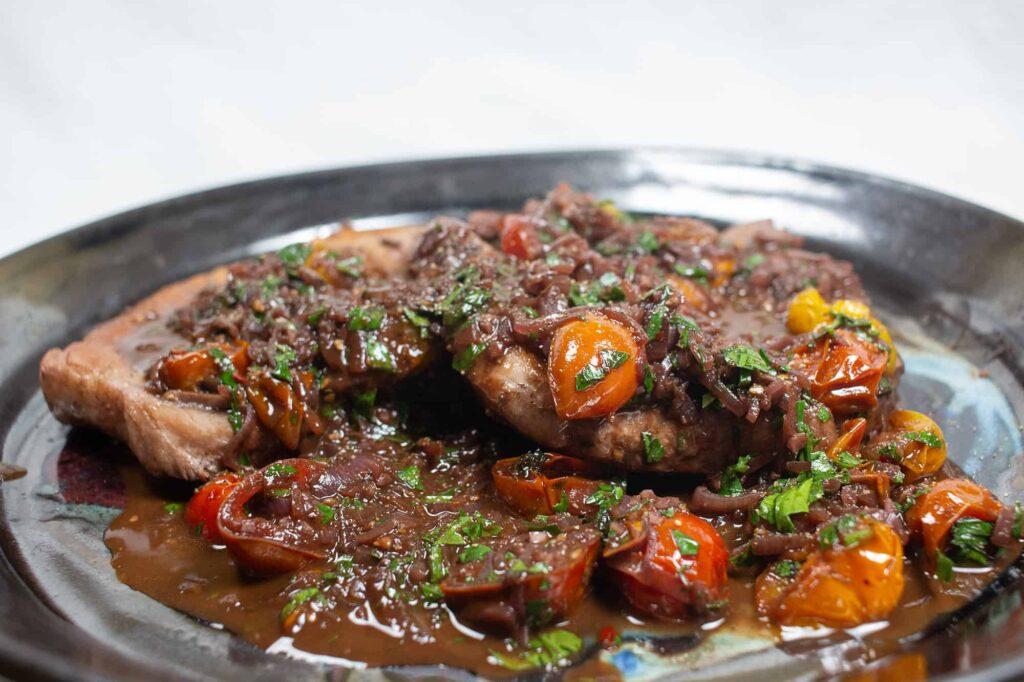 Pork chops and grape tomato sauce on a black plate.