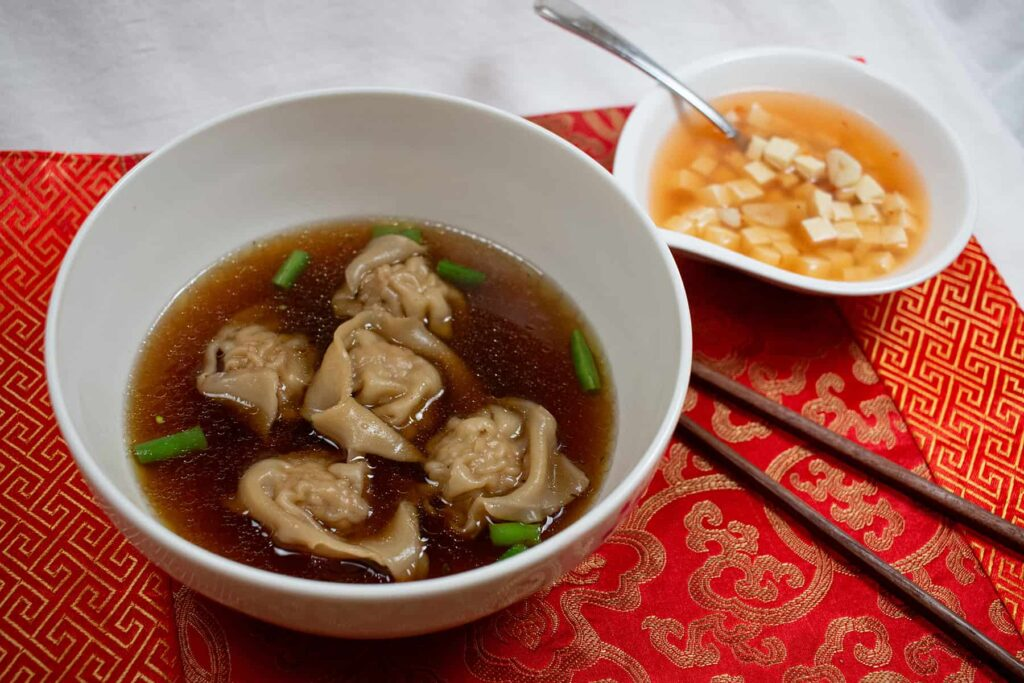 White bowl with dark broth and dumplings.