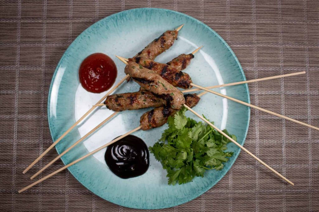 Blue plate with black and red sauces and grilled meat on a stick.