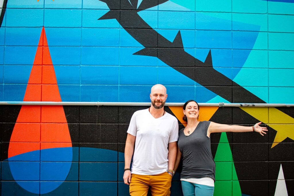 Two people standing against a colourful graffiti wall.
