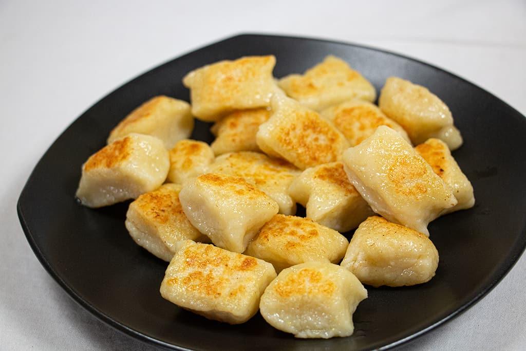 Fried gnocchi on a black plate.