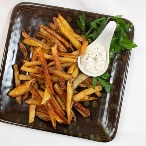 Crispy Fries and dill dip on a black plate