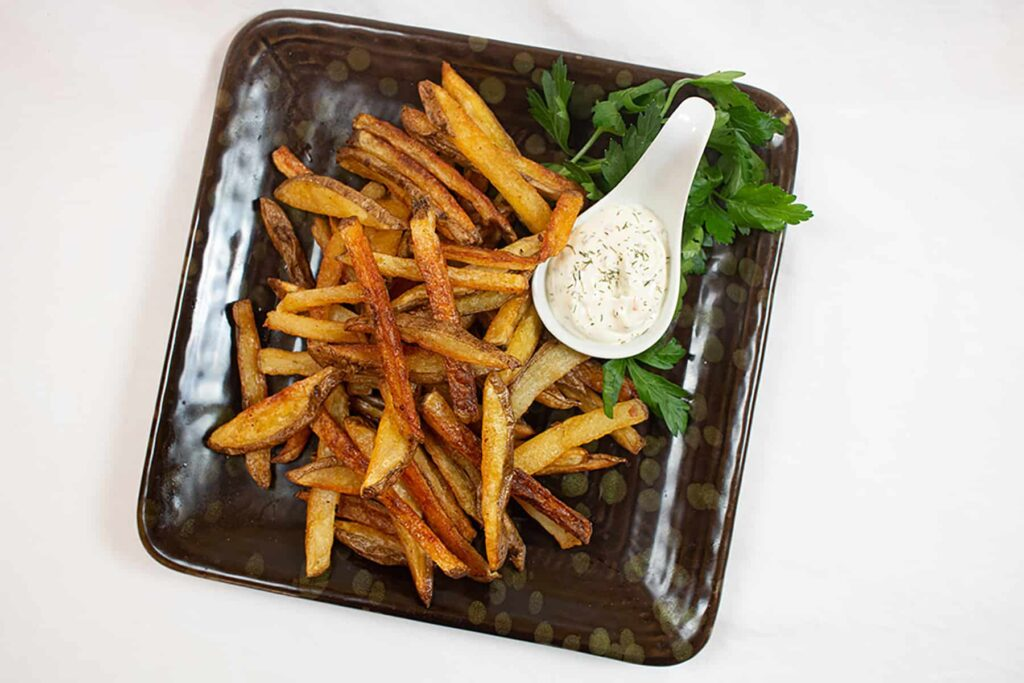 Crispy fries with dill dip on a black plate.