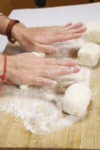 Hands rolling dough on a wooden cutting board.