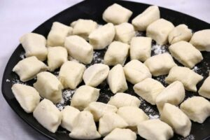 Uncooked gnocchi on a black plate.