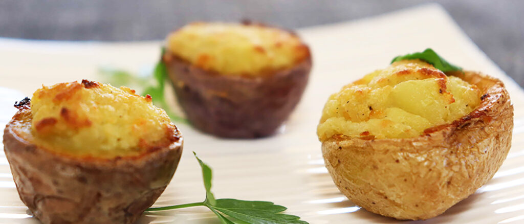 3 Pesto stuffed potatoes on a white plate.