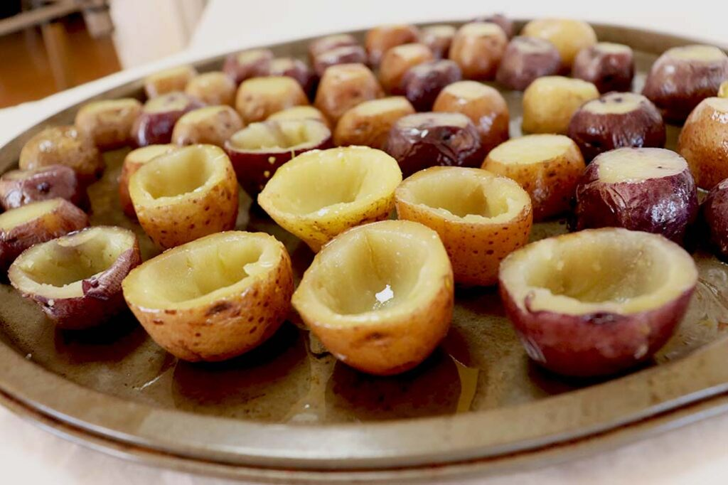 A pan of mini potatoes being hollowed out.