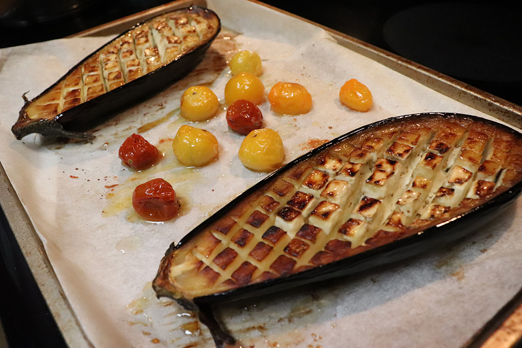 Eggplant on a roasting pan with cherry tomatoes